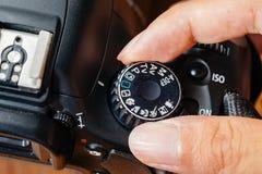 Funktionsläge för auto visartavla på dslrkamera med fingrar på visartavlan royaltyfria foton