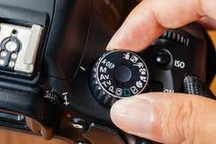 Funktionsläge för manuell visartavla på dslrkamera med fingrar på visartavlan royaltyfri fotografi