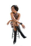 Funky 70s woman. Beautiful African woman in the seventies style sitting on stool and looking to side, isolated Royalty Free Stock Images