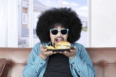 Funky Afro man holds cheeseburger Stock Images