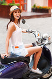 Funky beauty. Beautiful young woman in funky hat sitting on scooter and smiling stock photo