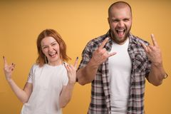 Funky crazy fellows show rock n roll gesture, yell from joy, rejoice hearing music of favourite band dressed in checkered shirt stock photography