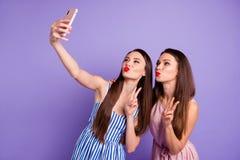 Funky divertente di due persone della foto alta vicina bello i suoi milllennials delle signore dei modelli telefona lo Smart Phon fotografia stock libera da diritti