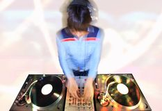 Funky female dj. Long-exposure image a funky female dj, mixing on turntables stock photography