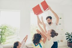 Funky, funny, positivity, rejoice, laugh concept. Daddy holds bi. G celebration christmas package above head, four kids up from comfort couch and try to reach royalty free stock image