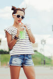 Funky girl drinking water against the sky Royalty Free Stock Photos