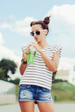 Funky girl drinking water against the sky Royalty Free Stock Photography