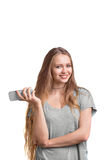 Funky girl in a gray T-shirt posing with a mobile phone. A young girl with a strong blonde hair, isolated on a white background. Cheerful, charming and Stock Photography