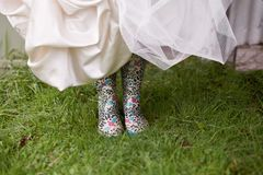 Funky Gumboots. A Bride lifts up her wedding dress to reveal funky colorful gumboots underneath Royalty Free Stock Photo