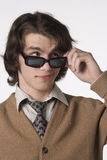 Funky guy with sunglasses. Young man dressed in retro clothes holds his sunglasses Royalty Free Stock Photos