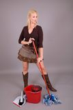 Funky housewife. Beautiful blond girl in sexy skirt mopping the floor Stock Images