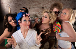 Funky housewife with rowdy group. Lady dancing with a very young group at a 1970s Disco Music Party Stock Image