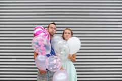 Funky jonge ballons van de paarholding tegen gestreepte achtergrond Het houdende van paar heeft wangen opgeblazen Stock Fotografie