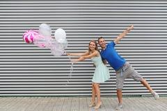 Funky jonge ballons van de paarholding terwijl het springen tegen gestreepte achtergrond Royalty-vrije Stock Foto