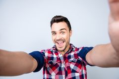 Funky mood of an excited geek young man in casual wear. He is ma. King selfie shot on camera, standing on a pure background, fooling around royalty free stock image