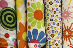 Funky Quilt Fabric. Fabric bolts of funky quilt fabric in bold bright colors with flowers, bullseye, star and box shapes in yellow, green, blue, red, orange and Royalty Free Stock Image