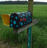 Funky rural mailbox. This cheery black and blue polka dot mail box stands out in spring wheat fields Royalty Free Stock Photo