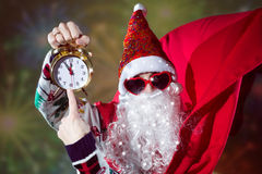 Funky Santa Claus with alarm clock wearing heart. Picture of funny Santa Claus with alarm clock wearing heart shape sunglasses on bright festive bokeh background Royalty Free Stock Image