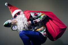 Funky Santa Claus with alarm clock wearing heart. Picture of funny Santa Claus with alarm clock wearing heart shape sunglasses on bright festive bokeh background Stock Image