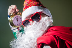 Funky Santa Claus with alarm clock wearing heart. Picture of funny Santa Claus with alarm clock wearing heart shape sunglasses on bright festive bokeh background Stock Images