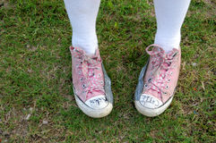 Funky Shoes. A girl wearing beat up pink shoes Royalty Free Stock Image