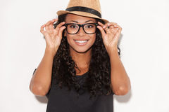 Funky style beauty. Portrait of beautiful young African woman in glasses and funky hat adjusting her glasses and smiling while standing against white background royalty free stock photos