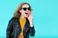 Funky stylish beautiful rocker Girl in leather jacket and black sunglasses. Punk is not dead. Attractive cool young woman shouting Royalty Free Stock Image