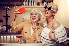 Funky trendy old women making selfie together while visiting bar stock photo