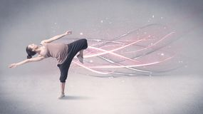Funky urban dancer with glowing lines. A pretty hip hop dancer dancing contemporary dance illustrated with glowing motion lines in the background concept Stock Photos