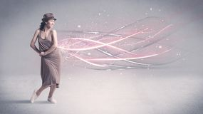 Funky urban dancer with glowing lines. A pretty hip hop dancer dancing contemporary dance illustrated with glowing motion lines in the background concept Royalty Free Stock Images