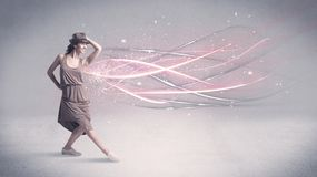 Funky urban dancer with glowing lines. A pretty hip hop dancer dancing contemporary dance illustrated with glowing motion lines in the background concept Royalty Free Stock Image