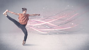 Funky urban dancer with glowing lines. A pretty hip hop dancer dancing contemporary dance illustrated with glowing motion lines in the background concept Royalty Free Stock Photo