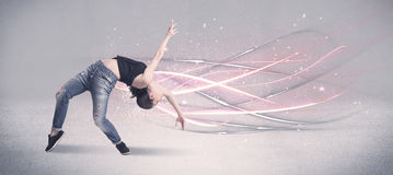 Funky urban dancer with glowing lines. A pretty hip hop dancer dancing contemporary dance illustrated with glowing motion lines in the background concept Royalty Free Stock Photos