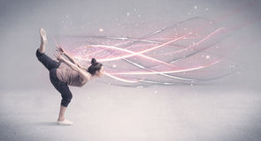 Funky urban dancer with glowing lines. A pretty hip hop dancer dancing contemporary dance illustrated with glowing motion lines in the background concept Stock Image