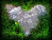 Valentine heart in grass. A heart in the green grass and flowers, with inscription Be my Valentine Royalty Free Stock Photo