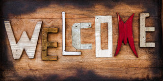 Funky Welcome Sign on Rustic Wooden Boards. A close up shot of a funky vintage welcome sign on a rustic wooden board background Royalty Free Stock Images