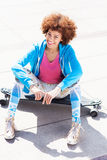 Funky woman sitting on skateboard Royalty Free Stock Image