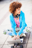 Funky woman sitting on skateboard with laptop Royalty Free Stock Image
