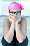 Funky woman wearing a neon pink headband and geek glasses. Stock Photos