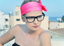 Funky woman wearing a neon pink headband and geek glasses. Royalty Free Stock Photography