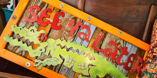 Funky Wooden See Ya Alligator Sign. A funky and whimsical wooden See Ya Later sign with a bright green alligator on the front Royalty Free Stock Photo