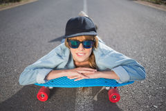 Funky young blonde lying on a deserted road Royalty Free Stock Photo