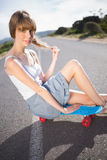 Funky young blonde sitting on her skateboard Royalty Free Stock Photography