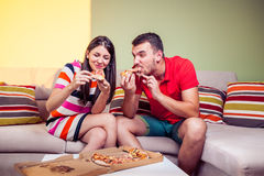 Funky young couple eating pizza on a couch Stock Photos