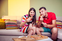 Funky young couple eating pizza on a couch Stock Photography
