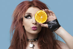 Funky young woman covering eye with sliced orange over blue background Royalty Free Stock Images