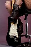 Funky young woman with her black hot guitar. Female legs in fishnet stockings and guitar stock photos
