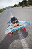 Funky young woman lying on a deserted road Royalty Free Stock Photos