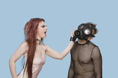 Funky young woman slapping man in gas mask over blue background Stock Images