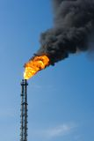 Funnel burning with thick smoke. Factory funnel burning with large flame and throwing thick cloud of smoke Stock Image
